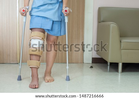 Patient standing on crutch in hospital ward ware knee brace support after do posterior cruciate ligament surgery ,Bandage on knee of asian woman on crutches.healthcare and medical concept. #1487216666