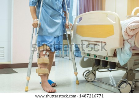 Patient standing on crutch in hospital ward ware knee brace support after do posterior cruciate ligament surgery ,Bandage on knee of asian woman on crutches.healthcare and medical concept. #1487216771
