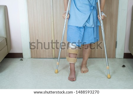 Patient standing on crutch in hospital ward ware knee brace support after do posterior cruciate ligament surgery ,Bandage on knee of asian woman on crutches.healthcare and medical concept. #1488593270