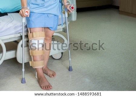 Patient standing on crutch in hospital ward ware knee brace support after do posterior cruciate ligament surgery ,Bandage on knee of asian woman on crutches.healthcare and medical concept. #1488593681