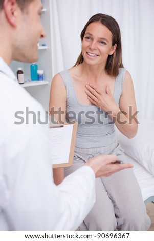 Patient talking to her doctor in examination room