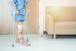 Patient try to walk with crutch in hospital ware knee brace support after do posterior cruciate ligament surgery ,Bandage on knee of asian woman on crutches.healthcare and medical concept.