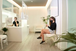 Patient waiting at the reception of the dental, gynecological or aesthetic clinic. The patient is using her smartphone while the receptionist takes a call. Medical concept.