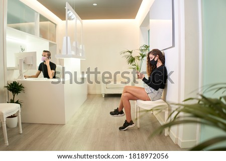 Patient waiting at the reception of the dental, gynecological or aesthetic clinic. The patient is using her smartphone while the receptionist takes a call. Medical concept. Foto stock ©
