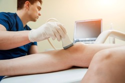 Patient with orthopedist doctor in his office. Knee sonography.