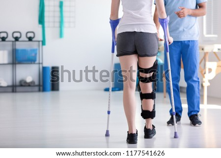 Patient with stiffener on the leg walking with crutches during rehabilitation Foto stock ©