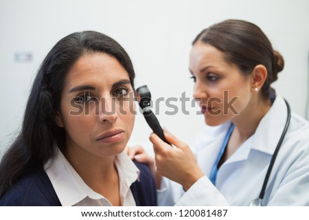 Patients ear being checked by doctor using otoscope in hospital