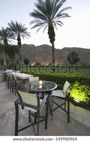 Patio chairs and tables against lawn and mountains in Palm Springs