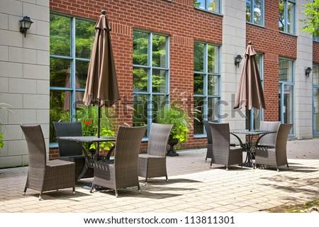 Patio furniture with umbrellas on stone patio near upscale condo building - stock photo