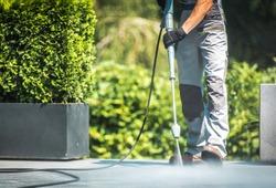 Patio Pressure Cleaning. Caucasian Men Washing His Concrete Floor Patio Using High Pressured Water Cleaner.