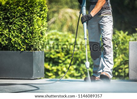 Patio Pressure Cleaning. Caucasian Men Washing His Concrete Floor Patio Using High Pressured Water Cleaner.