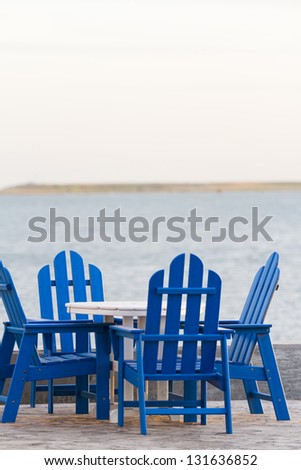 Pation with blue furniture on the beach.