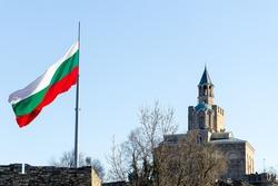 Patriarchal church at Tsarevets fortress, Veliko Tarnovo, Bulgaria and waving flag of Bulgaria