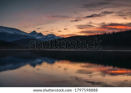 Patricia Lake with mountain range and the moon reflection at sunset. Jasper national park, Canada