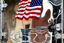 Patriotic abstract features an American flag decal on the polished metal door of a commercial trailer pulled by a semi-truck. Shiny doors reflect a nearby door and wall in distorted fashion.