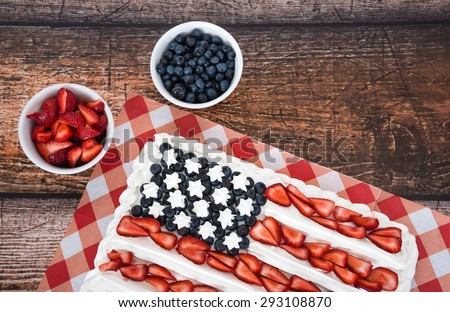 Patriotic American flag cake with blueberries and strawberries on vintage wooden background