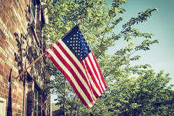 Patriotic American flag in front of a brick home, trees and blue sky background. Vintage filter effects.