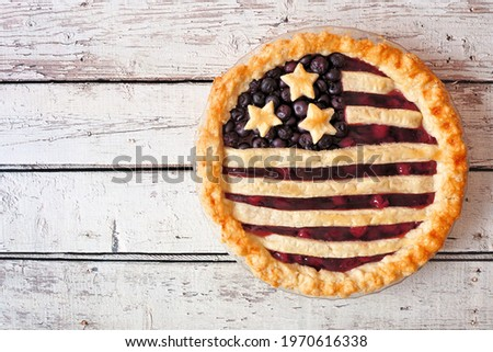 Patriotic American flag pie with cherries and blueberries. Above view on a rustic white wood background. Fourth of July food concept. Stock photo ©