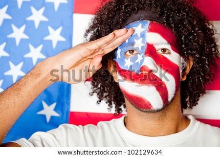 Patriotic American man with the USA flag painted on his face saluting