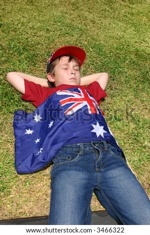 Patriotic Australian boy with Australian flag taking a short rest on grassy area.