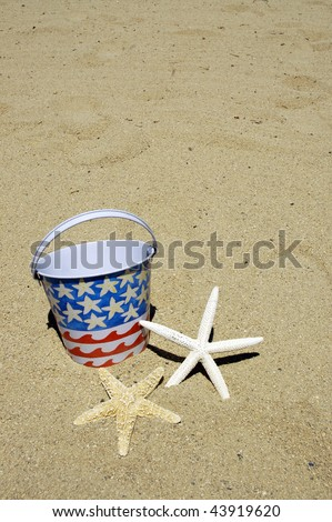 patriotic beach bucket and starfish on sand perfect for cover art