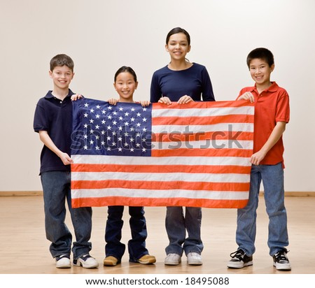 Patriotic children holding up the American flag together - stock photo