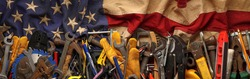 Patriotic collection of old and used work tools on worn US American flag. Made in USA, American workforce, or Labor Day concept.