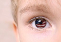 Patriotic concept. Little boy with reflection of American flag in eye, closeup