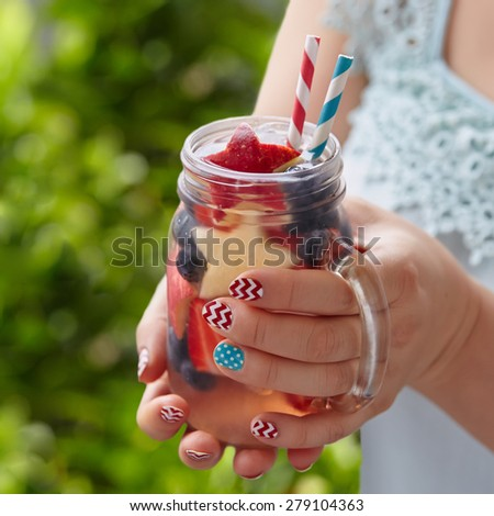 Patriotic drink cocktail with strawberry, blueberry and apple in woman\'s hands