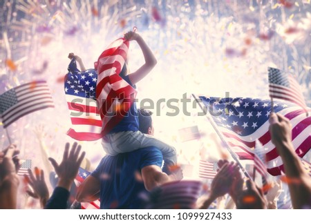 Patriotic holiday. Child sitting on shoulders of her father and  holding the Flag of the USA. America celebrate 4th of July. #1099927433