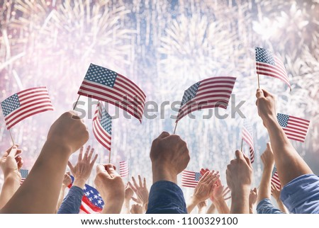 Patriotic holiday. Hands of people holding the Flags of the USA. America celebrate 4th of July.