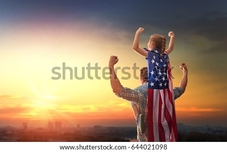 Shutterstock Patriotic holiday. Happy family, father and his daughter child girl with American flag outdoors on background sunset cityscape. USA celebrate 4th of July.