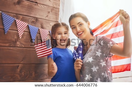 Patriotic holiday. Happy family, mother and her daughter child girl with American flag at home. USA celebrate 4th of July. #644006776