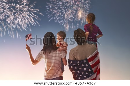 Patriotic holiday. Happy family, parents and daughters children girls with American flag outdoors. USA celebrate 4th of July. #435774367