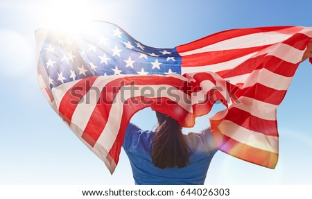 Patriotic holiday. Happy young woman with American flag. USA celebrate 4th of July.
