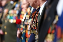 Patriotic holiday in honor of the anniversary of the end of the war, veterans are congratulated, the old soldiers with a lot of medals and orders are holding flowers, the memory of the dead