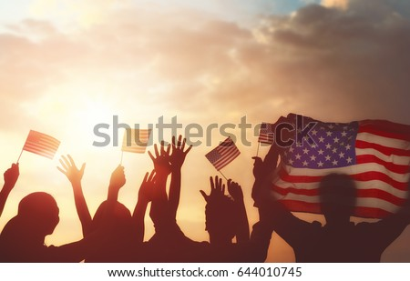 Patriotic holiday. Silhouettes of people holding the Flag of USA. America celebrate 4th of July.