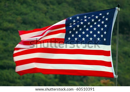 Patriotic Image of an American Flag Flapping in the Wind Against a Green Background