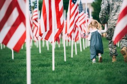 Patriotic Little girl walking with her dad in uniform holding 2 small American Flags in her hand
