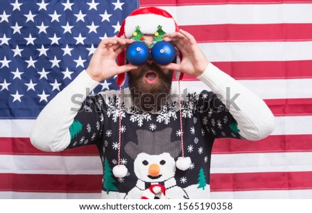 Patriotic surprise. Surprised hipster hold baubles as glasses. Bearded man look with surprise. Santas surprise celebration. Creating fun surprise. Christmas and new year. Holiday season.
