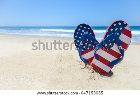 Patriotic USA background with flip flops on the sandy beach #647153035