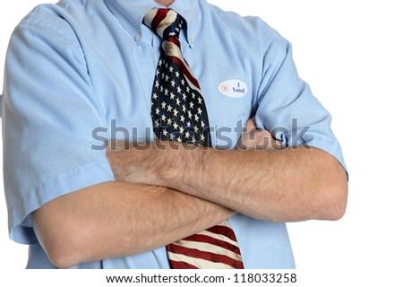 "Patriotic voter wearing a U.S. flag tie and dress shirt sporting an ""I voted"" sticker crosses his arms in a close up"