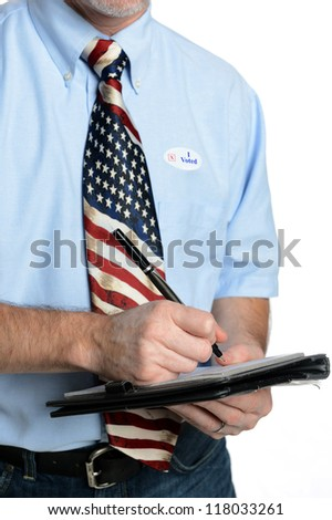 """Patriotic voter wearing a U.S. flag tie and dress shirt sporting an """"I voted"""" sticker puts pen to pad to fill out form, poll, ballot or survey"""