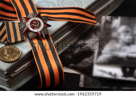 Patriotic War Order and battle order for courage and bravery on George Ribbon at old photos album with black and white photos background for the great day of Victory (russian text: Patriotic War)