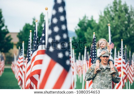 Patriotic 2 year old girl sitting on the shoulders of her American soldier dad smiling at the camera