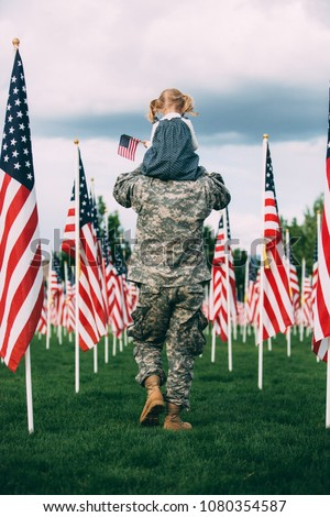 Patriotic 2 year old girl sitting on the shoulders of her American soldier dad, walking among American flags