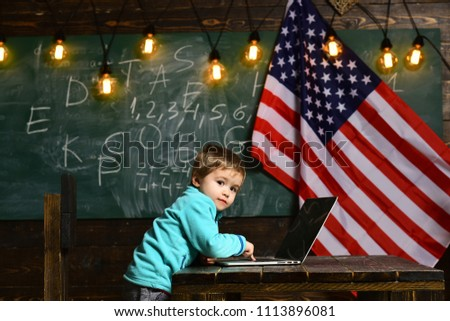 Patriotism and freedom. patriotism of small kid work on laptop with american flag #1113896081