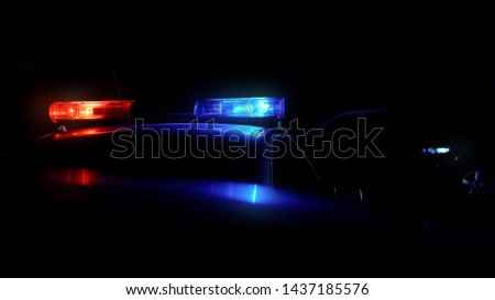 Patrol car driving along night city with flashing lights #1437185576