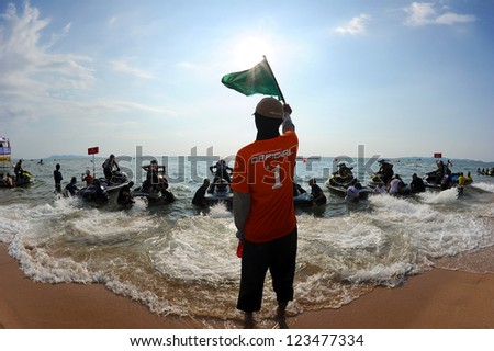 PATTAYA CITY THAILAND-DECEMBER 7:Unidentified The Official show the green flag start  class Pro-Am Runabout Open the Jetski  King's Cup World Cup Grand Prix at Jomtien Beach on Dec7, 2012 in,Thailand.