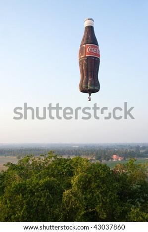 PATTAYA- DECEMBER 12: Hot-air balloon shaped as a Coca-Cola bottle flies during Pattaya International Balloon Fiesta 2009 in Pattaya, Thailand on December 12, 2009.